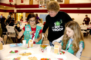 Sylvia Herrera 10 with Ginger Grzyb 10 from Girl Scout troop 70031 are showing Laurie McAbee their Gingerbread house They are making. This is the 25 and last year. Methodist Church Goodrich Dec 3, 16