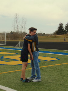 Scott greets son Reilly after running the first leg in the 4 by 800 meter relay on April 12.